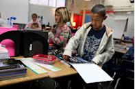 <p>Elementary school students take out their new supplies on the first day of class for the new year.</p>