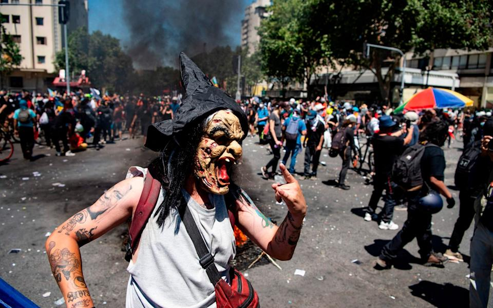 A demonstrator wearing a witch mask commemorates the first anniversary of the social uprising in Chile - AFP