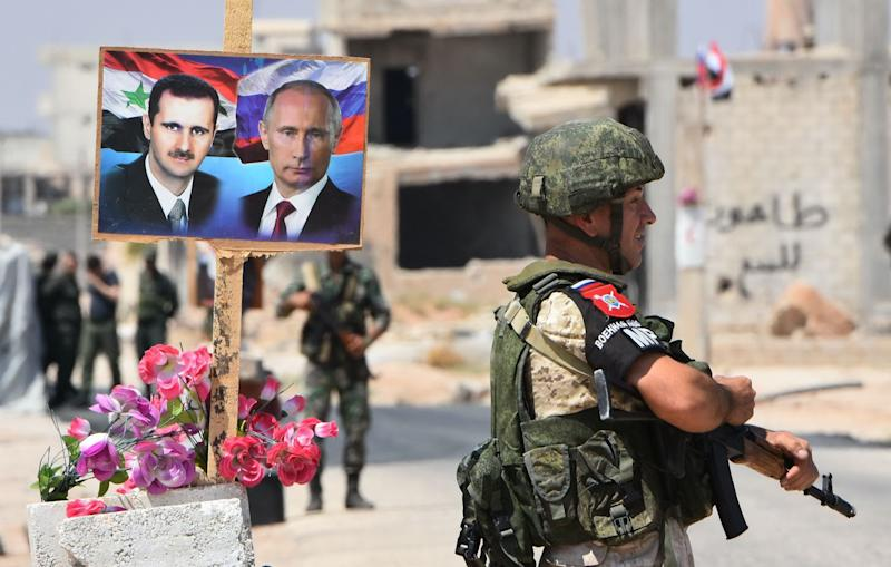 Members of Russian and Syrian forces stand guard near posters of Syrian President Bashar al-Assad and his Russian counterpart Vladimir Putin at the Abu Duhur crossing on the eastern edge of Idlib province on August 20, 2018. (Photo: GEORGE OURFALIAN/AFP/Getty Images)
