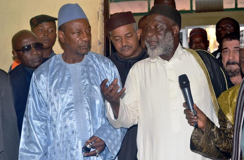 Guinean President Alpha Conde (L) and Imam of Conakry's Grand Mosque Elhadj Mamadou Saliou Camara (R) visit the morgue at the capital's Donka hospital on July 30, 2014, a day after a deadly stampede at a rap concert (AFP Photo/Cellou Binani)