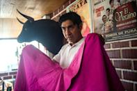 Bullfighter Fernando Villavicencio shows off the cloak he uses in corridas