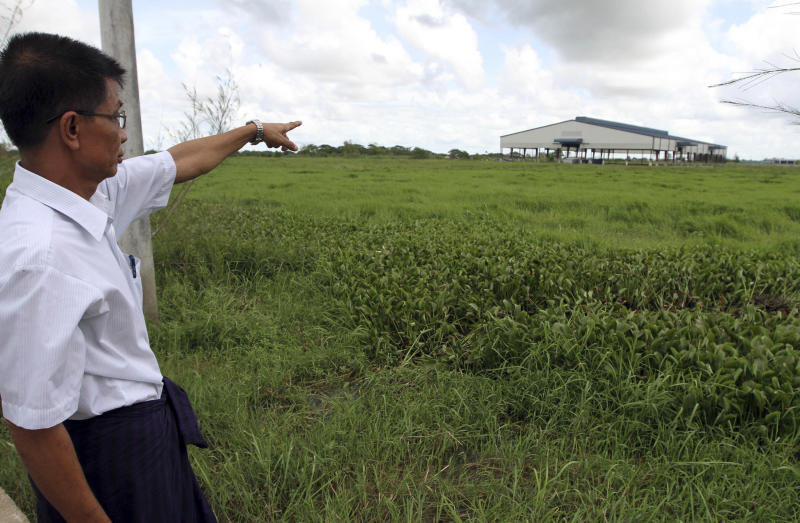 In this photo taken on Sept. 15, 2012, Myint Thein points out a land where his family used to farm at Mingaladon township, northern outskirts of Yangon, Myanmar. The landscape of Mingaladon township tells a story of economic upheaval. Skeletons of factories for a new industrial zone rise from thick green rice paddies local farmers say were seized illegally by the Zaykabar Company, one of Myanmar's most powerful companies. Human rights groups say land battles could intensify because companies tied to the military and business elite are rushing to grab land as the country emerges from five decades of isolation and opens its economy. (AP Photo/Khin Maung Win)
