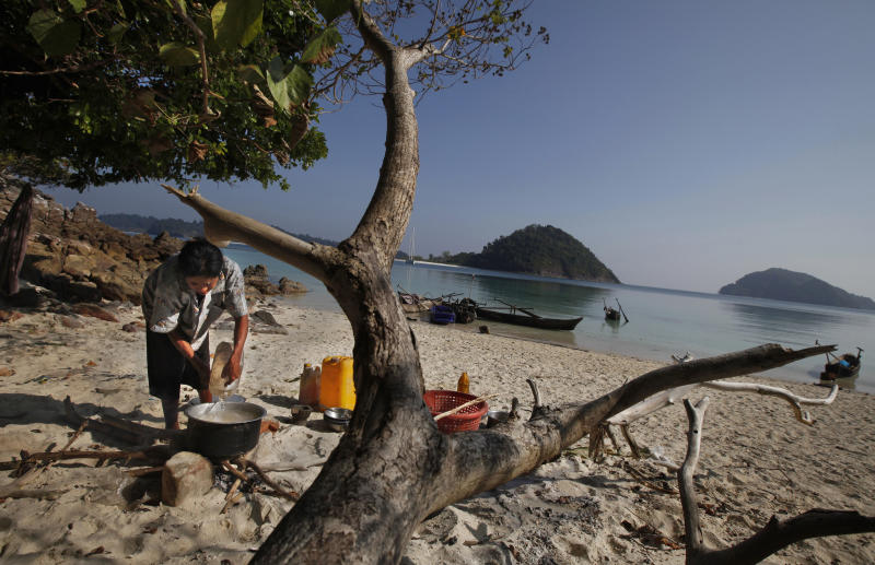 In this Sunday, Feb. 9, 2014 photo, a woman belonging to Moken tribe, nomads of the sea, cooks food in the shade of a tree on Island 115 in Mergui Archipelago, Myanmar. Isolated for decades by the country's former military regime and piracy, the Mergui archipelago is thought by scientists to harbor some of the world's most important marine biodiversity and looms as a lodestone for those eager to experience one of Asia's last tourism frontiers before, as many fear, it succumbs to the ravages that have befallen many of the continent's once pristine seascapes. (AP Photo/Altaf Qadri)