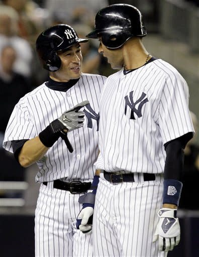 New York Yankees' Ichiro Suzuki, left, talks with Derek Jeter after they scored on Nick Swisher's fourth-inning grand slam in their baseball game against the Toronto Blue Jays at Yankee Stadium in New York, Thursday, Sept. 20, 2012. The Yankees won 10-7. (AP Photo/Kathy Willens)