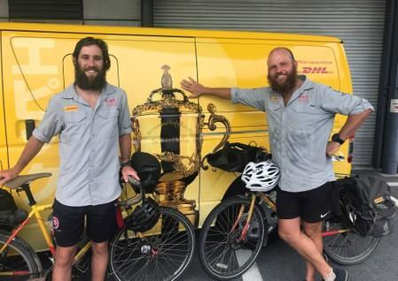 Cyclists James Owens and Ron Rutland pose with bicycles after reaching Osaka, following almost 20,000 kilometre trip from London to deliver Rugby World Cup whistle, in Osaka