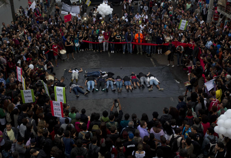 Protesters lie on a stretch of Brasil Avenue, depicting victims of a police operation at the Mare slum, in Rio de Janeiro, Brazil, Tuesday, July 2, 2013. The police operation aimed to capture an alleged looter, who according to police killed an officer after a peaceful protest. At least nine people died and two suspects were captured during the June 25th operation, according to the police. (AP Photo/Silvia Izquierdo)