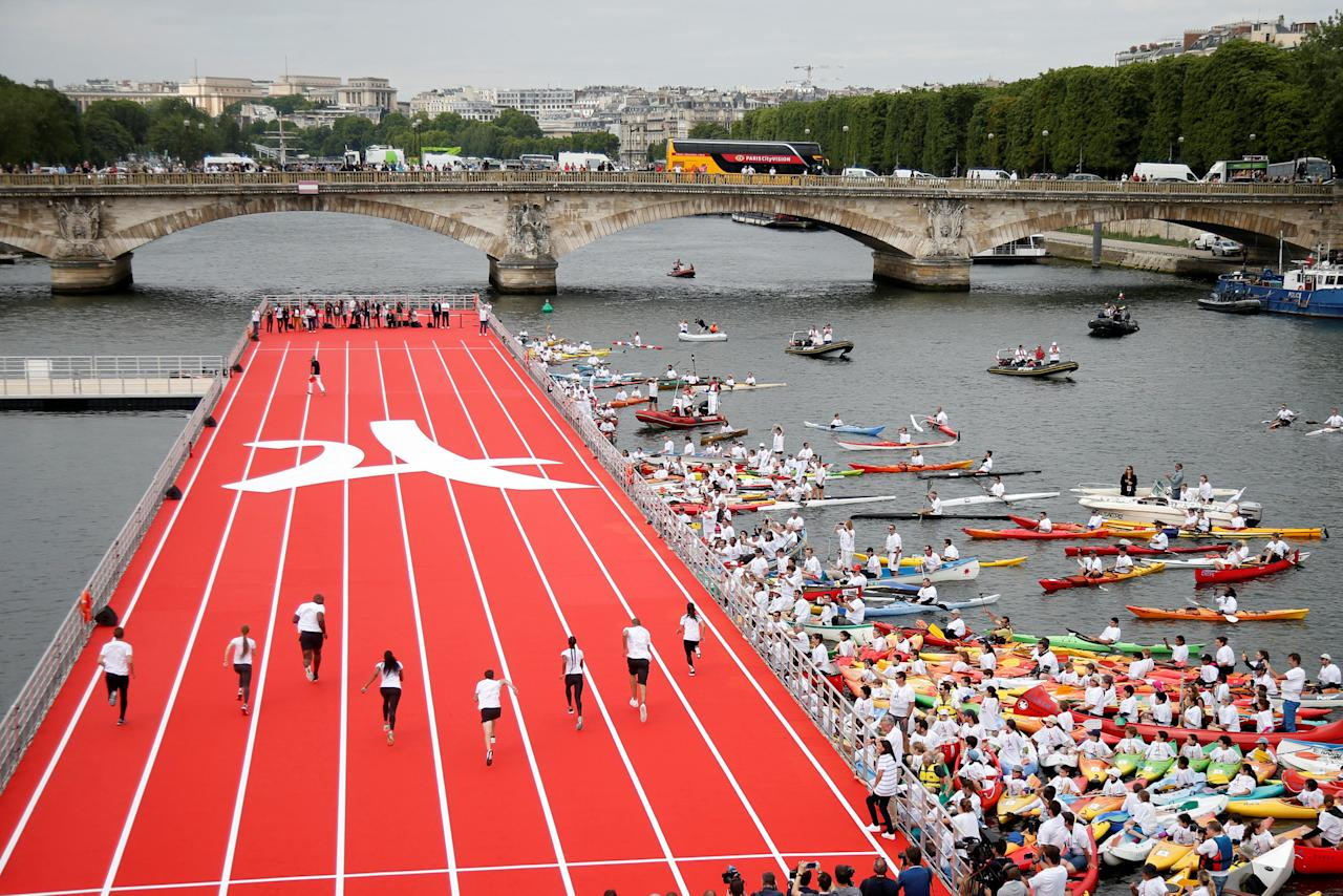 Runners compete on an athletics track that floats on the River Seine, in Paris, France, June 23, 2017 as Paris is transformed into a giant Olympic park to celebrate International Olympic Days with a variety of sporting events for the public across the city during two days as the city bids to host the 2024 Olympic and Paralympic Games.  REUTERS/Charles Platiau     TPX IMAGES OF THE DAY