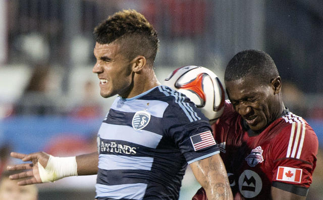 Sporting Kansas City forward Dom Dwyer, left, heads the ball past Toronto FC defender Doneil Henry, right, during second-half MLS soccer game action in Toronto, Saturday, July 26, 2014. (AP Photo/The Canadian Press, Nathan Denette)