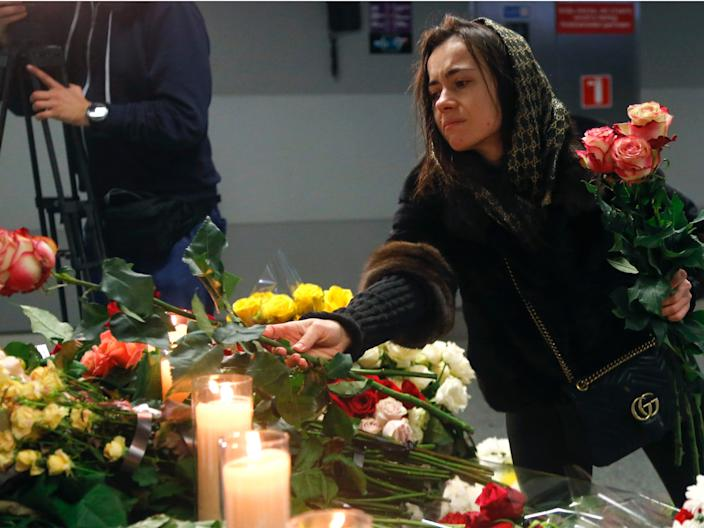 A woman lays flowers at a memorial of the flight crew members of the Ukrainian 737-800 plane that crashed on the outskirts of Tehran, at Borispil international airport outside in Kyiv, Ukraine, Saturday, Jan. 11, 2020. Ukraine's President Volodymyr Zelenskiy says that Iran must take further steps following its admission that one of its missiles shot down Ukrainian civilian airliner.  (AP Photo/Efrem Lukatsky)