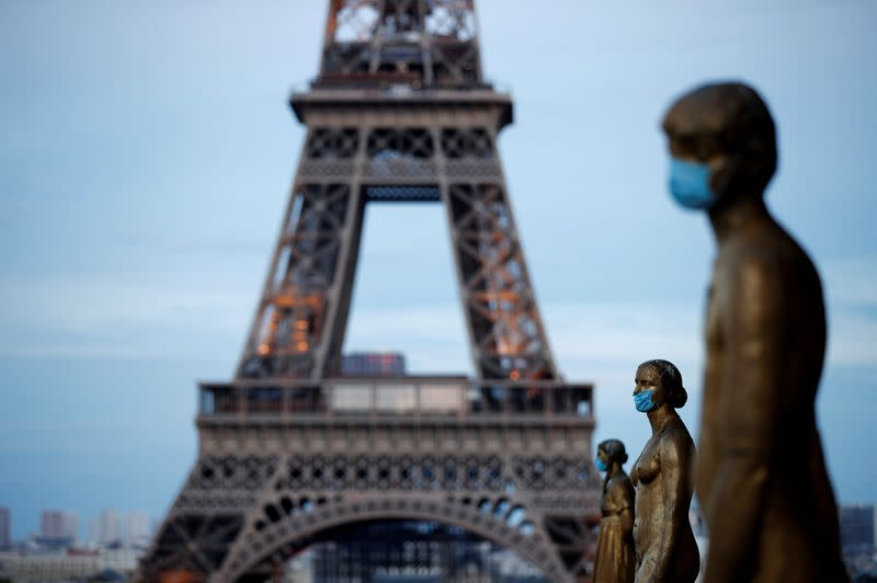 FILE PHOTO: Golden Statues at the Trocadero square near the Eiffel tower wear protective masks during the outbreak of the coronavirus disease