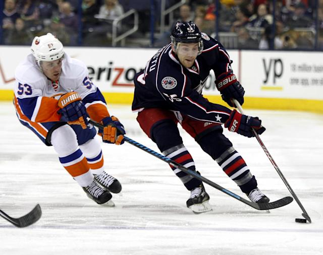 Columbus Blue Jackets' Mark Letestu, right, controls the puck in front of New York Islanders' Casey Cizikas in the second period of an NHL hockey game in Columbus, Ohio, Sunday, April 6, 2014. (AP Photo/Paul Vernon)