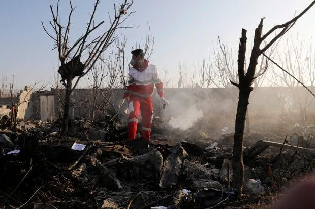 A rescue worker searches the area where Flight PS752 crashed in Shahedshahr, southwest of the capital Tehran, Iran, Wednesday, Jan. 8, 2020.