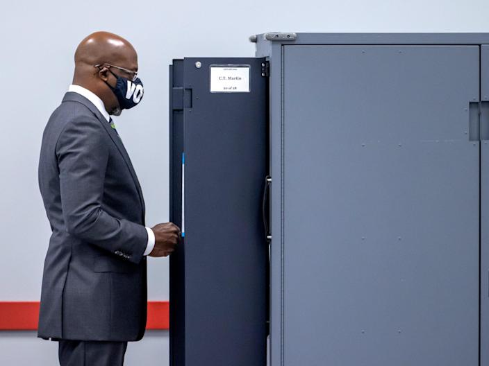 <p>Democratic US Senate candidate Raphael Warnock casts his ballot on the first day of voting in the Georgia runoffs</p> (EPA)
