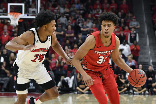Youngstown State forward Michael Akuchie (31) attempts to drive past the defense of Louisville forward Dwayne Sutton (24) during the first half of an NCAA college basketball game in Louisville, Ky., Sunday, Nov. 10, 2019. (AP Photo/Timothy D. Easley)
