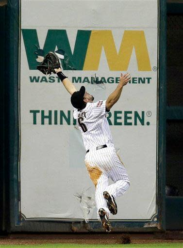 Houston Astros left fielder Travis Buck (6) leaps to catch a fly ball hit by New York Mets' Andres Torres during the fifth inning of a baseball game Monday, April 30, 2012, in Houston. Torres was out on the play. (AP Photo/David J. Phillip)