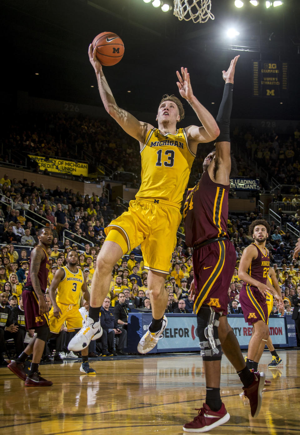FILE - In this Jan. 22, 2019, file photo, Michigan forward Ignas Brazdeikis (13) goes to the basket, defended by Minnesota forward Eric Curry (24), in the second half of an NCAA college basketball game, in Ann Arbor, Mich. Brazdeikas was Newcomer of the Year in the Big Ten Conference, Tuesday, March 12, 2019. (AP Photo/Tony Ding, File)