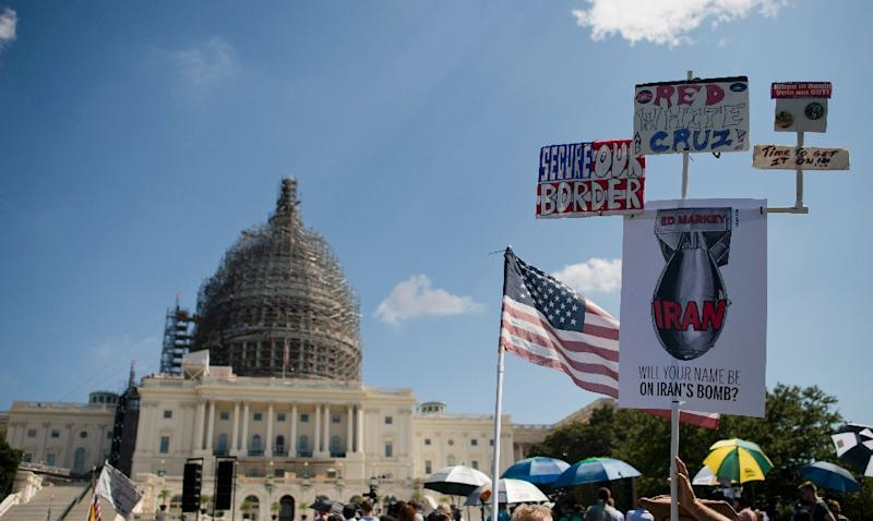 Protesters hold up signs during a rally against the international nuclear agreement with Iran outside the US Capitol in Washington, DC on September 9, 2015 (AFP Photo/Andrew Caballero-Reynolds)