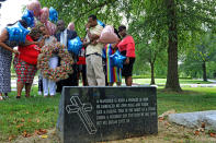 FILE - In this Friday, Aug. 9, 2019 file photo, Lesley McSpadden, the mother of Michael Brown, prays with a group from Rainbow of Mothers, before placing a large wreath at her son's grave on the fifth anniversary of this death, at St. Peter's Cemetery in St. Louis. At left is Samaria Rice, the mother of Tamir Rice, who was killed by police in 2014 in Ohio. At center is Ben Crump, her attorney, and at right, her husband, Louis Head. (Laurie Skrivan/St. Louis Post-Dispatch via AP)