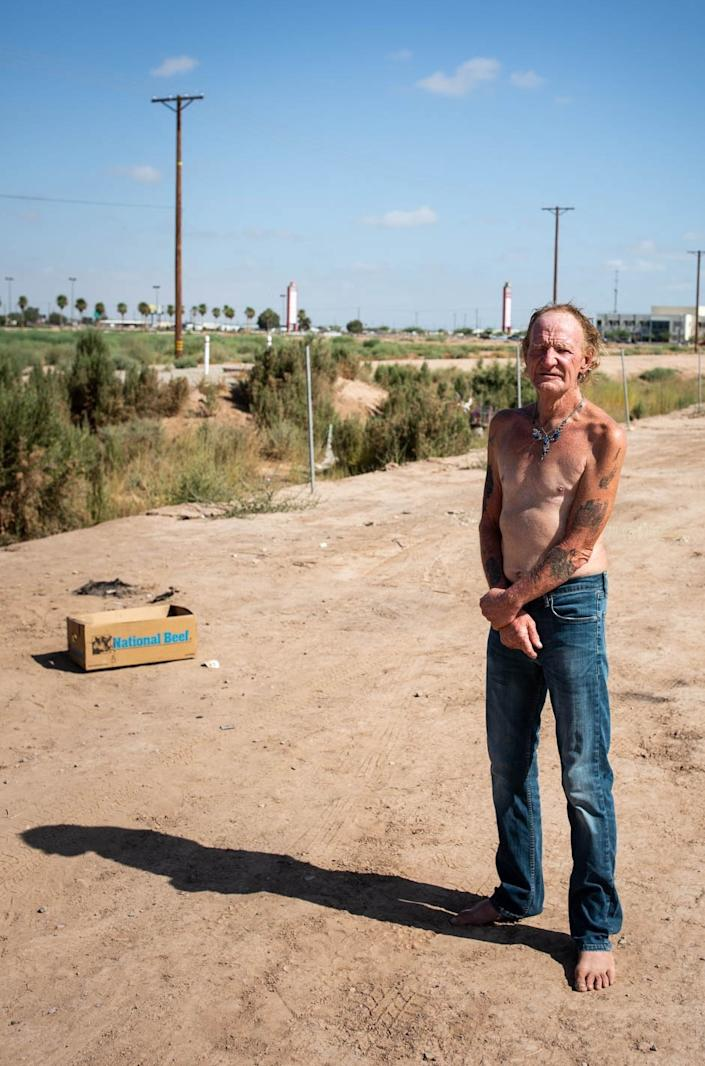 """Carl Wilkinson lives on a stretch of dirt not far from Imperial County's indoor mall. He probably qualifies for a COVID hotel room through Project Roomkey but said he lost his ID and has not tried applying. <span class=""""copyright"""">(Anna Maria Barry-Jester / Kaiser Health News)</span>"""