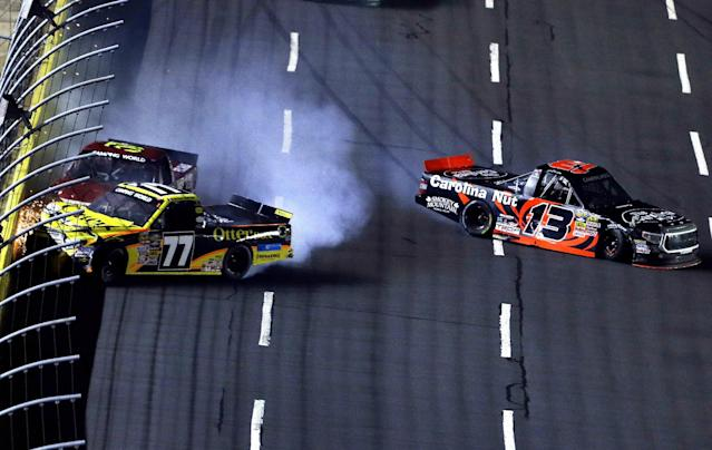 German Quiroga (77) and Norm Benning collide with the wall on the front stretch as Jeb Burton (13) avoids a collision at right during the closing laps of the NASCAR Truck series auto race in Concord, N.C., Friday, May 16, 2014. Kyle Busch won the race. (AP Photo/Gerry Broome)