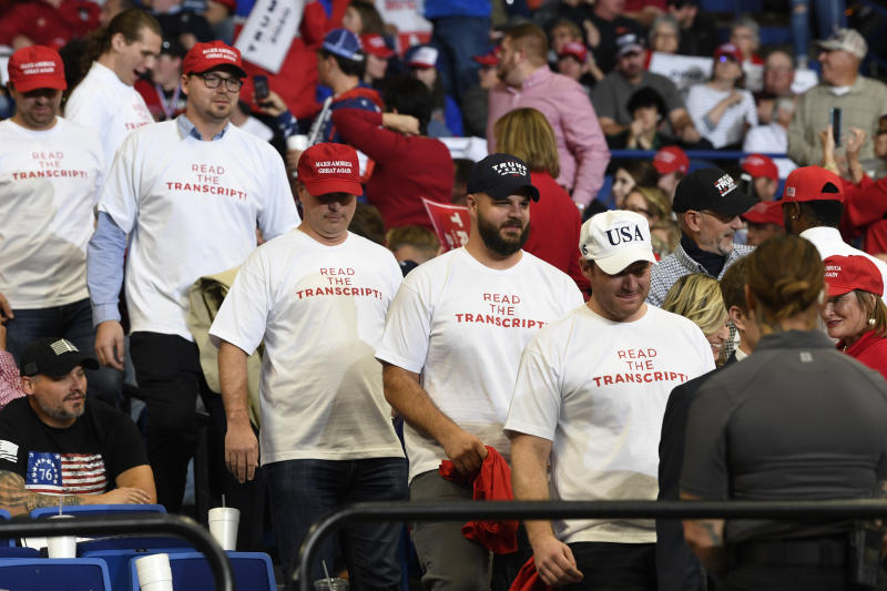 """People wearing shirts with the words """"Read the Transcript"""" arrive to attend a campaign rally with President Donald Trump in Lexington, Ky., Monday, Nov. 4, 2019. (AP Photo/Susan Walsh)"""