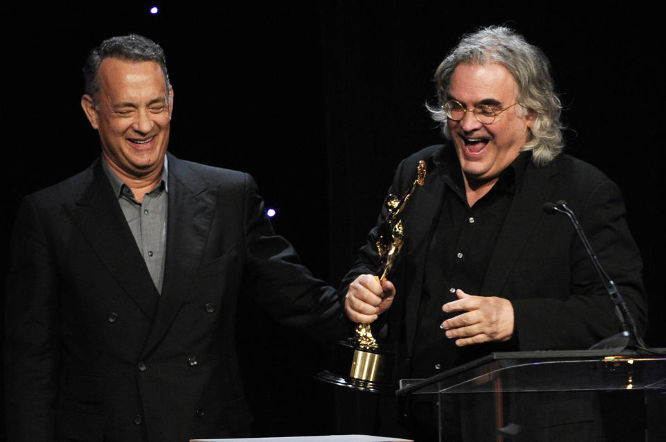 Tom Hanks, left, presents the Golden Eddie award to Paul Greengrass at the 64th Annual ACE Eddie Awards, on Friday, Feb. 7, 2014, in Beverly Hills, Calif. (Photo by Chris Pizzello/Invision/AP)