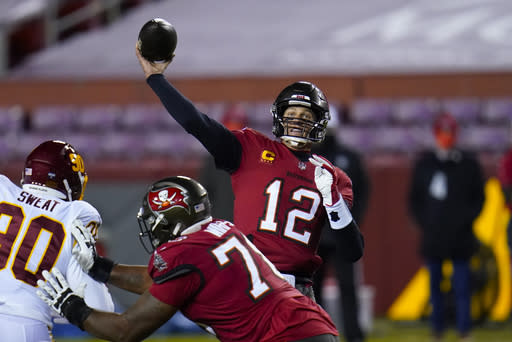 Tampa Bay Buccaneers quarterback Tom Brady (12) throwing a touchdown pass to wide receiver Antonio Brown during the first half of an NFL wild-card playoff football game against the Washington Football Team, Saturday, Jan. 9, 2021, in Landover, Md. (AP Photo/Julio Cortez)
