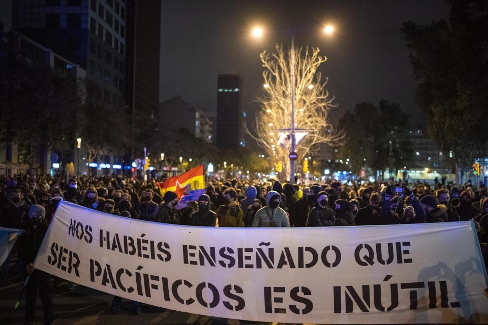 "Demonstrators march holding a banner reading ""you have taught us that being peaceful is useless"" during a protest condemning the arrest of rap singer Pablo Hasel in Barcelona, Spain, Sunday, Feb. 21, 2021. The imprisonment of Pablo Hasel for inciting terrorism and refusing to pay a fine after having insulted the country's monarch has triggered a social debate and street protests. (AP Photo/Emilio Morenatti)"