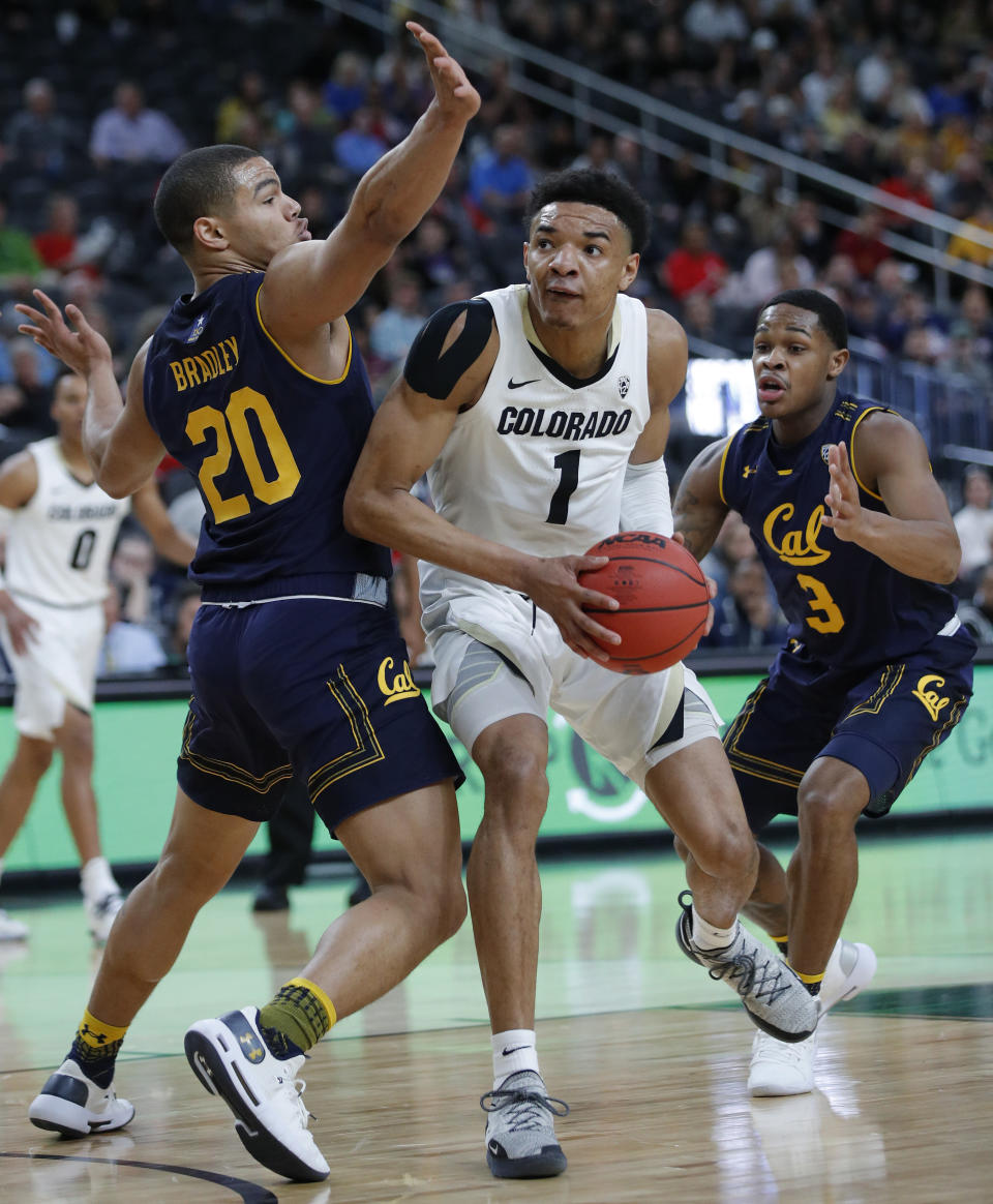 Colorado's Tyler Bey drives through California's Matt Bradley, left, and California's Paris Austin during the first half of an NCAA college basketball game in the first round of the Pac-12 men's tournament Wednesday, March 13, 2019, in Las Vegas. (AP Photo/John Locher)