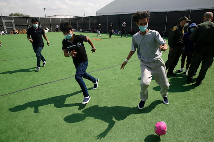 Minors play soccer on a field at the Department of Homeland Security holding facility run by the Customs and Border Patrol (CBP) on March 30, 2021 in Donna, Texas. The Donna location is the main detention center for unaccompanied children coming across the U.S. border in the Rio Grande Valley. The children are housed by the hundreds in eight pods that are about 3,200 square feet in size. Many of the pods had more than 500 children in them. The youngest of the unaccompanied minors are kept separate from the rest of the detainees. The Biden administration has just allowed journalists inside its main detention facility at the border for migrant children. It is an overcrowded tent structure where more than 4,000 kids and families are kept in pods, with the youngest kept in a large play pen with mats on the floor for sleeping. (Photo by Dario Lopez-Mills - Pool/Getty Images)
