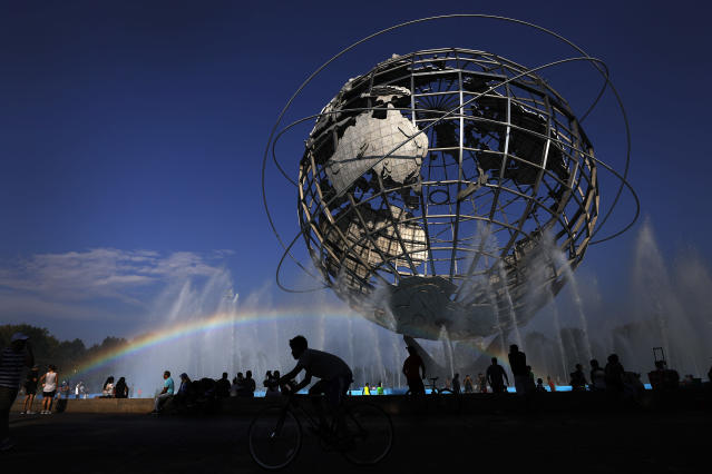 <p>A cyclist passes under a rainbow at the Unisphere fountain inside Flushing Meadows Corona Park outside the US Open tennis tournament, Monday, September 3, 2018, in New York. (AP Photo/Adam Hunger) </p>