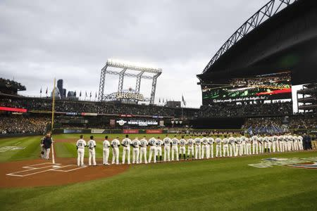 Mar 29, 2018; Seattle, WA, USA; Members of the Seattle Mariners (right) and Cleveland Indians stand during the national anthem before the season opener at Safeco Field. Mandatory Credit: Joe Nicholson-USA TODAY Sports