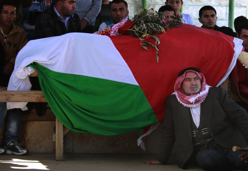 A Palestinian man sits next the body of Zakariya Abu Eram, covered with a Palestinian flag, during his funeral in the West Bank town of Yatta, near Hebron, Friday, March 9, 2012. According to the Israeli military, a Palestinian stabbed an Israeli soldier in the neck during a raid in the town of Yatta, seriously wounding him. The soldier opened fire, wounding the assailant and killing Eram who was not involved in the attack, witnesses said. The Israeli military claim he was the attacker's accomplice. (AP Photo/Nasser Shiyoukhi)