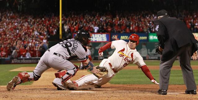 St. Louis Cardinals' Allen Craig is tagged by Boston Red Sox catcher Jared Saltalamacchia but he is ruled safe with the game-winning run due to interference when he tried to leave third base in the ninth inning during Game 3 of the World Series between the St. Louis Cardinals and the Boston Red Sox on Saturday, Oct. 26, 2013, at Busch Stadium in St. Louis. At right is home plate umpire Dana DeMuth. (AP Photo/St. Louis Post-Dispatch, Chris Lee)