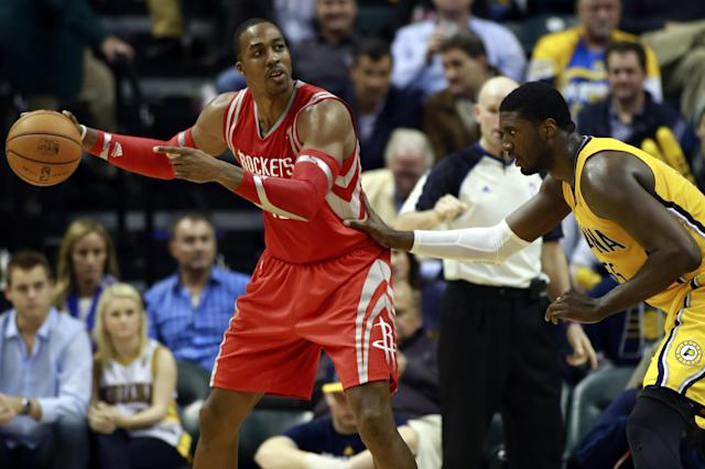 Houston Rockets center Dwight Howard, left, controls the basketball guarded by Indiana Pacers center Roy Hibbert in the second half of an NBA basketball game in Indianapolis, Friday, Dec. 20, 2013. (AP Photo/R Brent Smith)