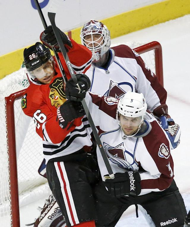 Colorado Avalanche defenseman Nate Guenin (5) and Chicago Blackhawks center Michal Handzus battle in front of goalie Jean-Sebastien Giguere during the first period of an NHL hockey game Friday, Dec. 27, 2013, in Chicago. (AP Photo/Charles Rex Arbogast)