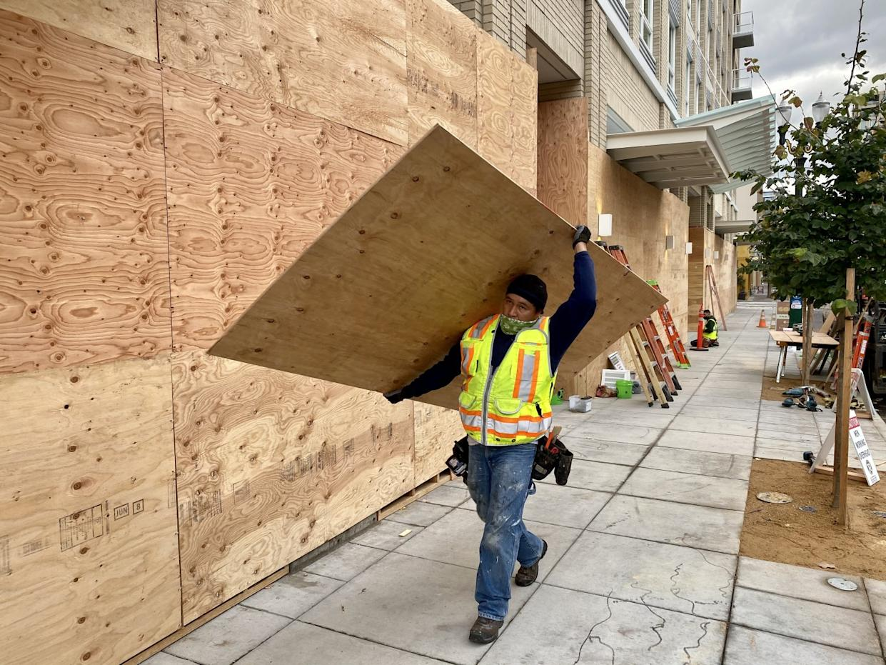 A worker carries plywood to clad the base of a Portland condominium tower Nov. 5 in case of post-election violence.