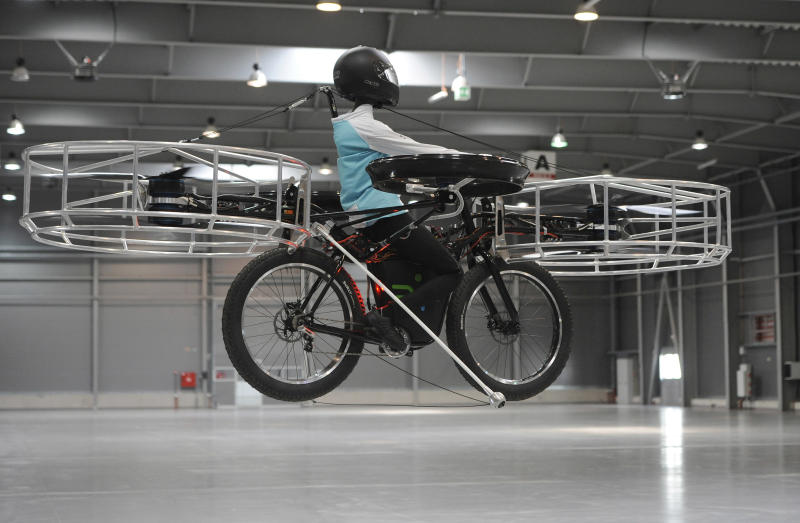 The remote-controlled Flying Bike with a test dummy flies during its presentation in Prague on Wednesday, June 12, 2013. Three Czech companies have teamed up to make a prototype of an electric bicycle that can fly. Controlled remotely, the bike carrying a figurine successfully took off Wednesday inside a large exhibition hall in Prague and landed safely after a five-minute flight. (AP Photo/CTK, Stanislav Zbynek) SLOVAKIA OUT