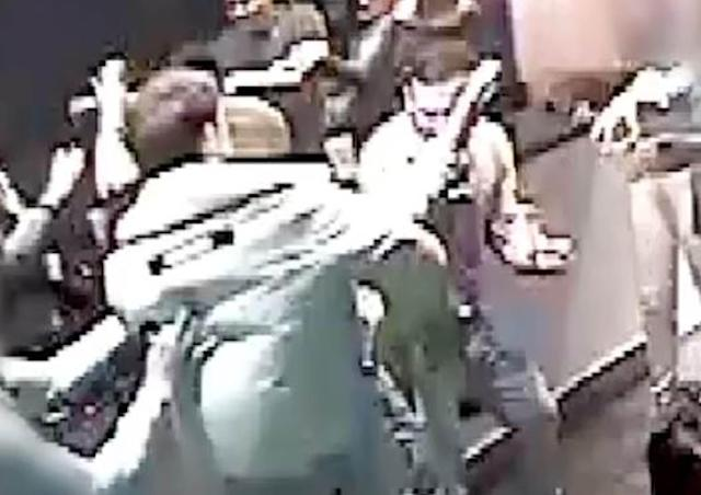 O'Brien (back to camera) during the attack on 21-year-old Josh Hanson (facing camera) who puts his hand up seconds after being slashed in the neck (PA)