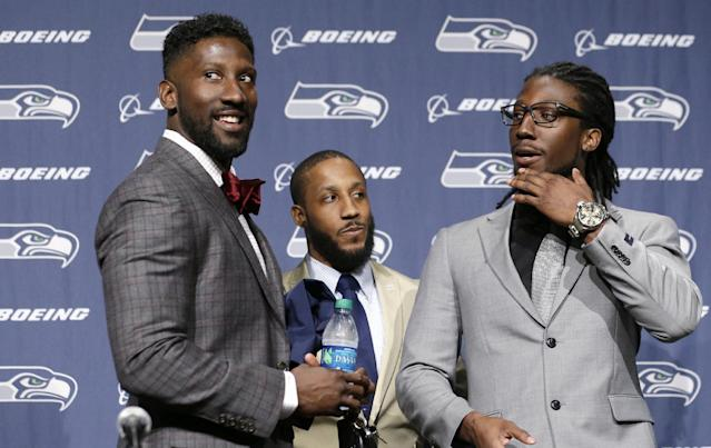 Seattle Seahawks' Marcus Trufant, left, is joined by his brothers Isaiah, center, and Desmond after a news conference announcing his retirement from football after signing with the team a day earlier, Thursday, April 24, 2014, in Renton, Wash. Marcus Trufant started 125 games in a Seattle career that lasted from 2003 to 2012. The cornerback was a first-round pick in 2003 out of Washington State and immediately moved into the starting lineup, playing a key role on the 2005 team that advanced to the franchise's first Super Bowl. (AP Photo/Elaine Thompson)