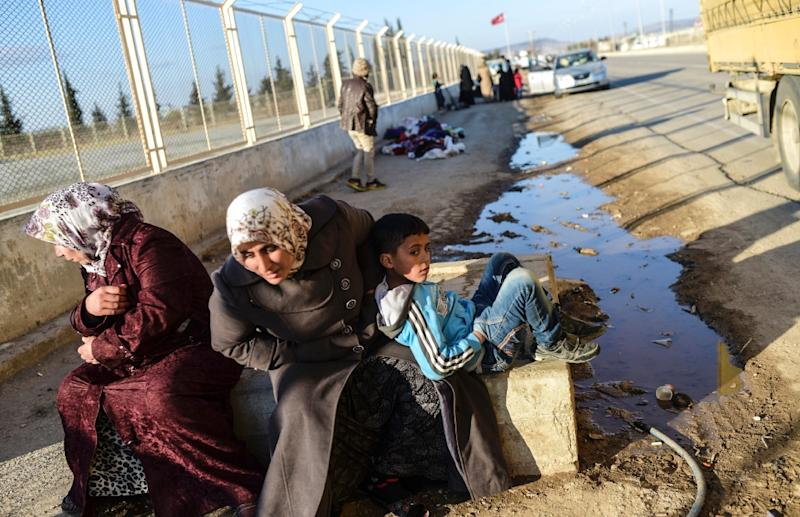 Two Syrian women and a boy wait in front of Oncupinar crossing gate,  near the town of Kilis, to return to Syria on February 9, 2016