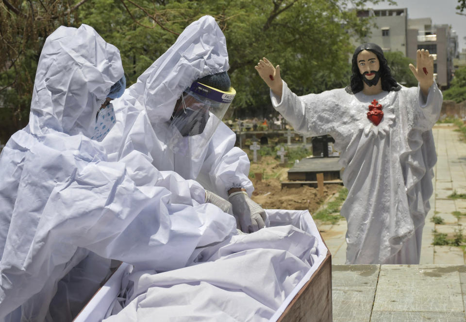 Body of a COVID-19 victim is prepared for burial at a Christian cemetery in New Delhi, India, Saturday, May 29, 2021. India's death toll is the third-highest reported in the world after the U.S. and Brazil. (AP Photo/Ishant Chauhan)