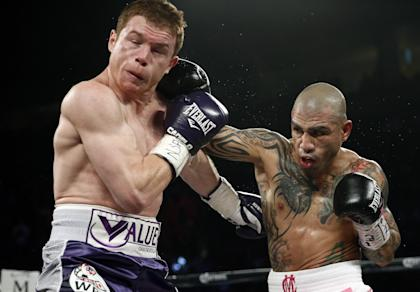 Miguel Cotto hits Canelo Alvarez during their bout Saturday night. (AP)