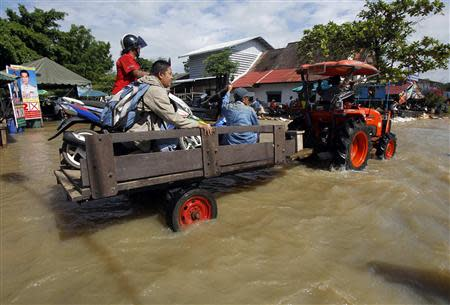Residents sit on a loader as it makes its way down a flooded street at Srimahaphot district in Prachin Buri province, east of Bangkok September 24, 2013. REUTERS/Chaiwat Subprasom