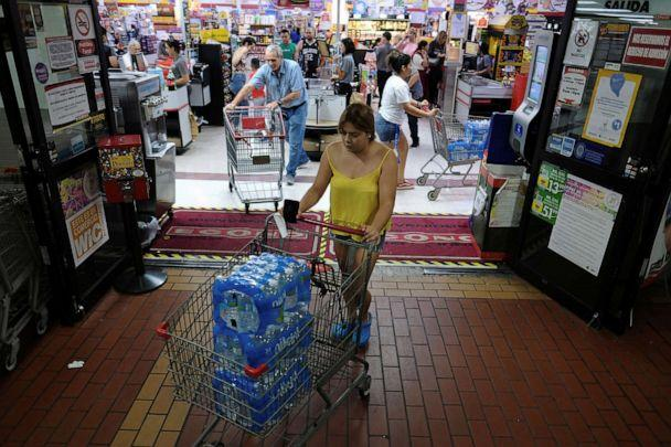 PHOTO: A woman purchases bottled water from a local grocery store as Tropical Storm Dorian approaches in Cabo Rojo, Puerto Rico, Aug. 26, 2019. (Ricardo Arduengo/Reuters)