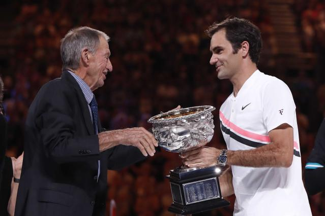 Tennis - Australian Open - Men's singles final - Rod Laver Arena, Melbourne, Australia, January 28, 2018. Switzerland's Roger Federer is presented with the trophy by former player Ashley Cooper after winning the final against Croatia's Marin Cilic. REUTERS/Issei Kato