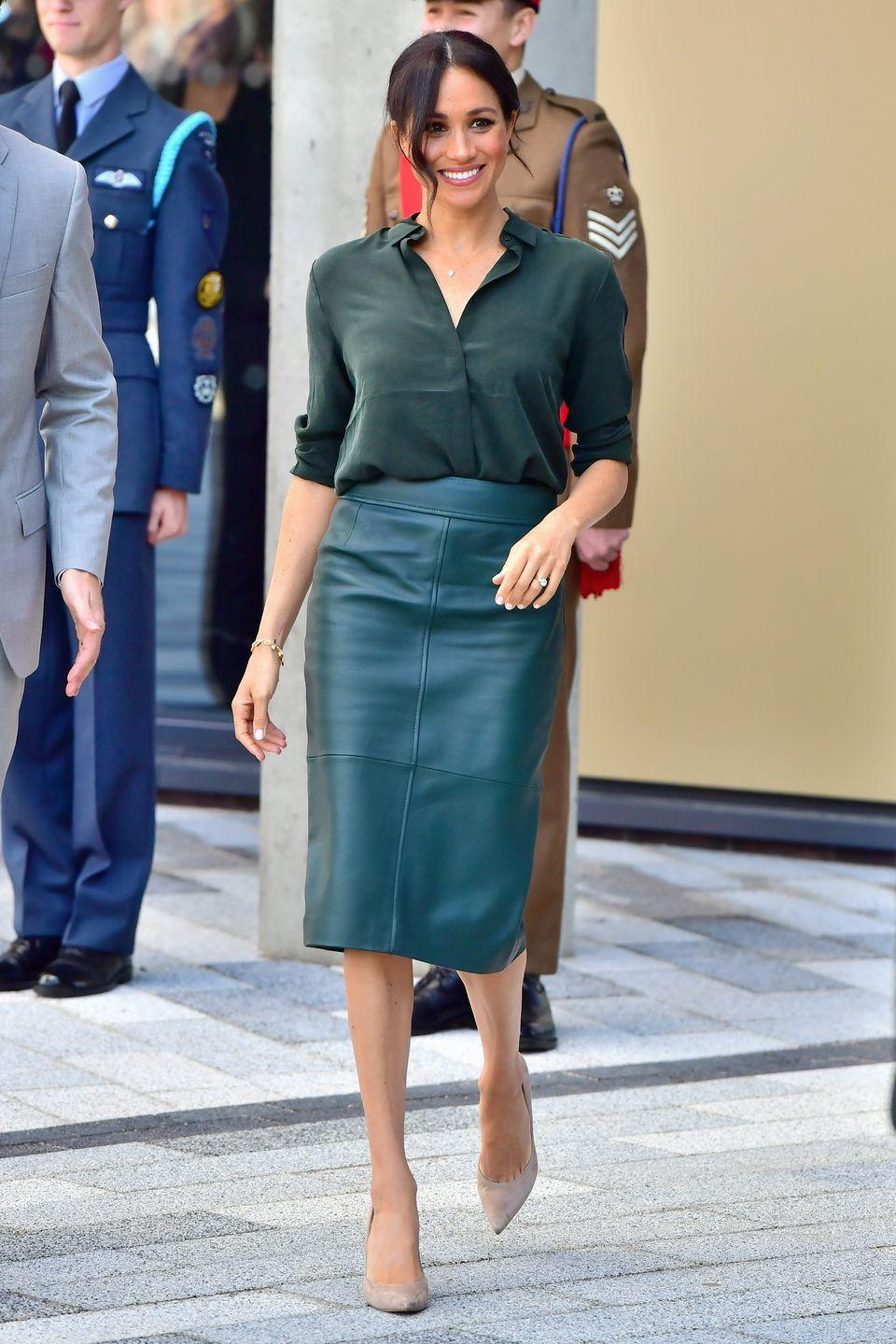 <p>Meghan Markle wore a Merida-esque look with a modern twist in 2018 with her hunter green monochromatic leather skirt and button-down blouse combination.</p>