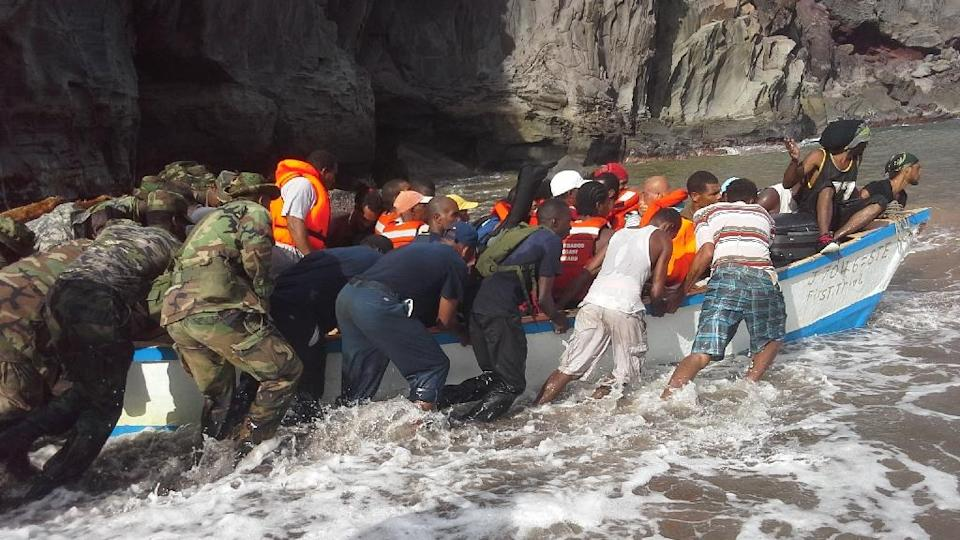Rescuers assist villagers in a boat during evacuation efforts in Petite Savannah, Dominca, which was the hardest hit town by Tropical Storm Erika on August 31, 2015 (AFP Photo/Carlisle Jno Baptiste)