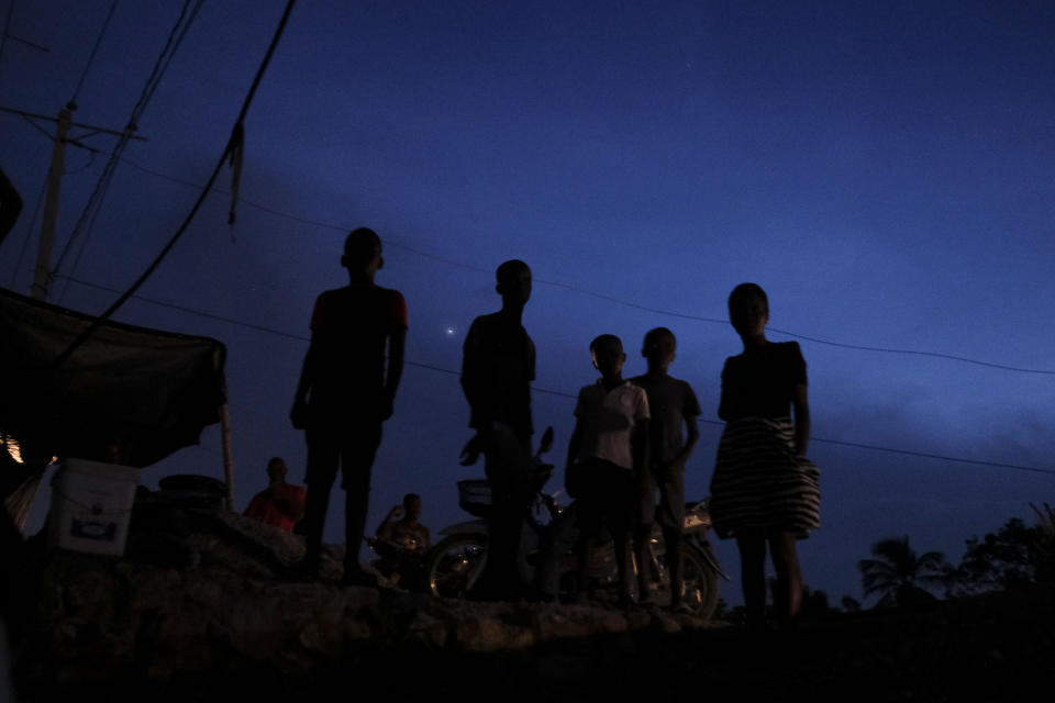 People who now sleep outside after their homes were damaged by the earthquake stand at sunset in Les Cayes, Haiti Sunday, Aug. 22, 2021, a week after a 7.2 magnitude quake. (AP Photo/Matias Delacroix)