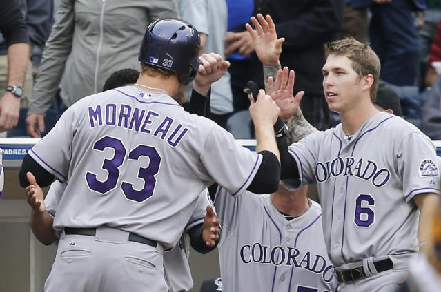 Colorado Rockies' Justin Morneau is met by Corey Dickerson, right, and others after scoring against the San Diego Padres during the seventh inning of a baseball game Thursday, April 17, 2014, in San Diego. (AP Photo/Lenny Ignelzi)